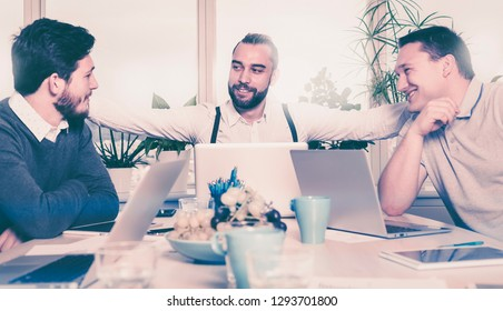 three men during a meeting are happy about signing the contract of a joint venture. hipster boss hugs employees