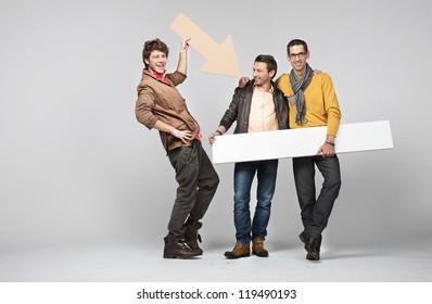 Three men with empty board and arrow