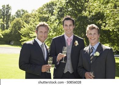 Three men in garden, wearing full suits, holding wineglasses, portrait