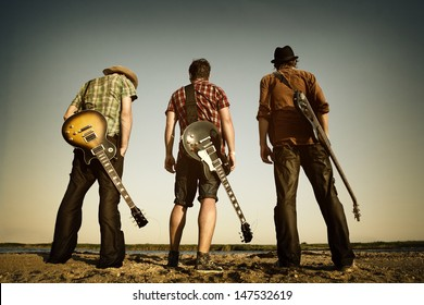 Three men with guitars on the river.