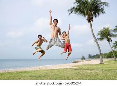 Three men jumping in air, looking at camera