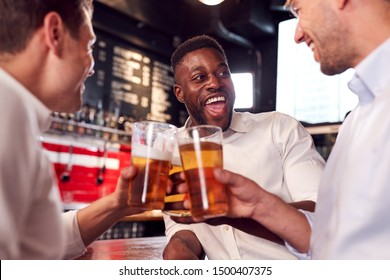 Three Men Making A Toast As They Meet For Drinks And Socialize In Bar After Work