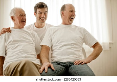 Three men from a multi generational family laughing together inside a room.