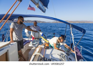 Three men are on the boat. All of them have white tops with sunglasses and swimming shorts