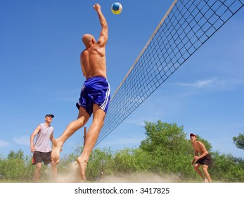 Three men playing beach volleyball - balding man strikes ball with fist. Shot near Dnieper river, Ukraine.