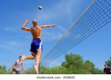 Three men playing beach volleyball - balding man moves muscular shoulder back to hit the ball. Shot near Dnieper river, Ukraine.