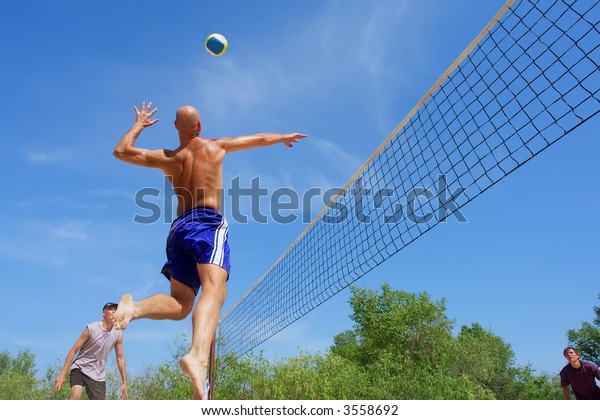Three men playing beach volleyball - balding man moves muscular shoulder back to hit the ball. Shot near Dnieper river, Ukraine.
