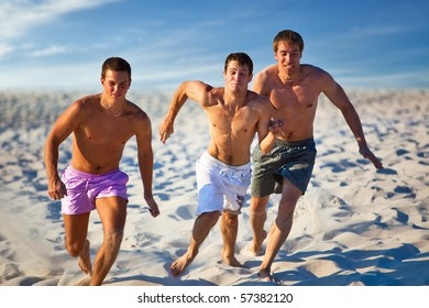 Three men run competition on beach.