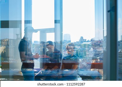Three men are seen through the glass. The reflection of the big city in the window is visible.
