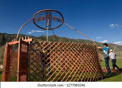 Three men setting up a yurt frame in pasture of Chilik river valley Saty, Kazakhstan - September 7, 2016