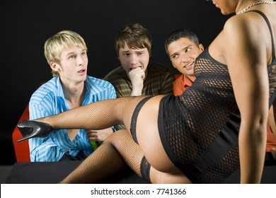 Three men sitting in front of woman in dark room. The are looking confused and shocked. Front view