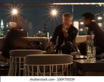 Three men sitting on a chic rooftop bar at night in Manhattan. Stools and table, large string lights along the balcony, lights of New York City in the background. Low light photography, motion blur.