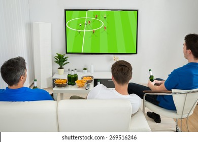 Three Men Sitting On Couch Watching Football Match On Television