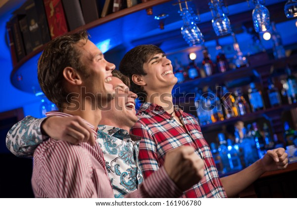 Three men stand in a row embracing smile and look in front of you, sports fans