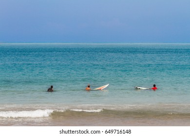 Three men waiting for a wave to surf at Barra beach in Salvador, Brazil