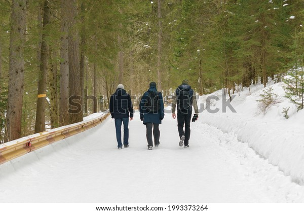 three-men-walk-along-road-600w-199337326