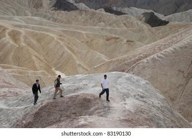 Three men walking around the desert in Death Valley, California, USA
