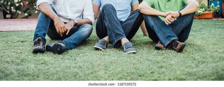 Three men wearing jeans sitting together on the grass. Close up shot of group of adults with smart casual dress relaxing on the green lawn.