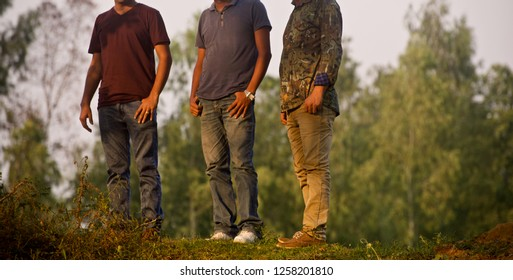 Three men wearing jeans standing in a place unique photo