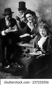 Three men and a woman eating watermelon, St, Paul, Minnesota, c.1910.