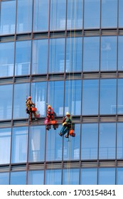 Three men workers in red and dark work clothes cleaning the exterior windows of a business skyscraper. Outdoor