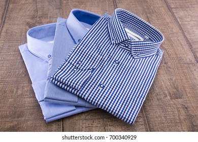 Three men's shirts folded on a wooden background