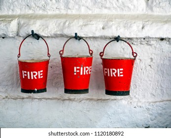 three metal fire buckets hanging on old whitewashed wall
