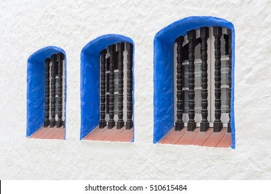 Three metal grilled windows with blue frames in mediterranean