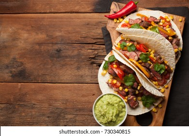 Three Mexican tacos with marbled beef, black Angus and vegetables on old rustic table. Mexican dish with sauces guacamole and salsa in bowls. Top view with copy space.