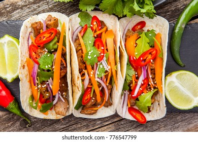 Three Mexican tacos with meat and vegetables. Top view.