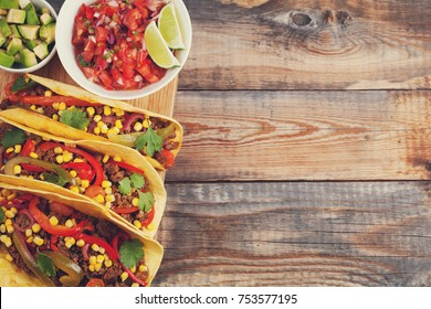 Three Mexican tacos with minced beef and mix vegetables on old rustic table. Mexican dish with sauce salsa in bowl and avocado. Spicy and hot street food. Top view with copy space.