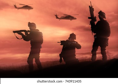 Three military soldiers silhouettes on sunset sky background.