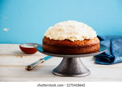 Three milk cake with mascarpone cream and coconut on blue background