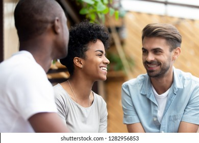 Three millennial multi-ethnic friends spending weekend together sitting in cafe or restaurant cozy summer terrace talking enjoying free time with each other, focus on laughing attractive african girl
