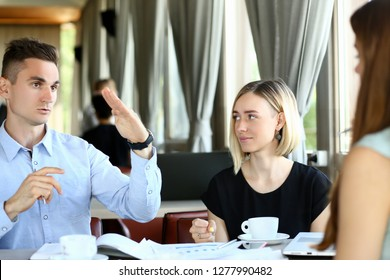 Three millennial people portrait met in cafe to discuss plans and tasks set by leadership during lunch break. Happy and successful use their time competently processing all for sake of the client