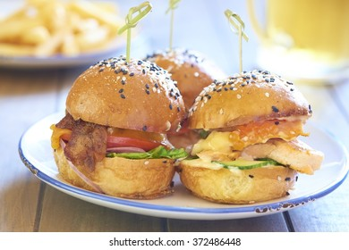 Three mini burgers with beef, chicken and fish