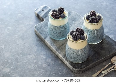 Three Mini Vegan Blue Spirulina Chia Puddings Topped with Whipped Coconut Cream and Frozen Berries