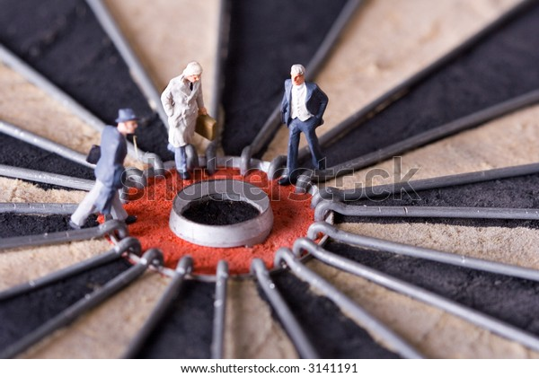 Three miniature businessman walking to the center of a dartboard. Shallow depth of field.