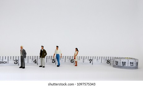 Three miniature men and a miniature woman standing in a row beside the extended tape measure. The concept of a gender gap in the workplace.