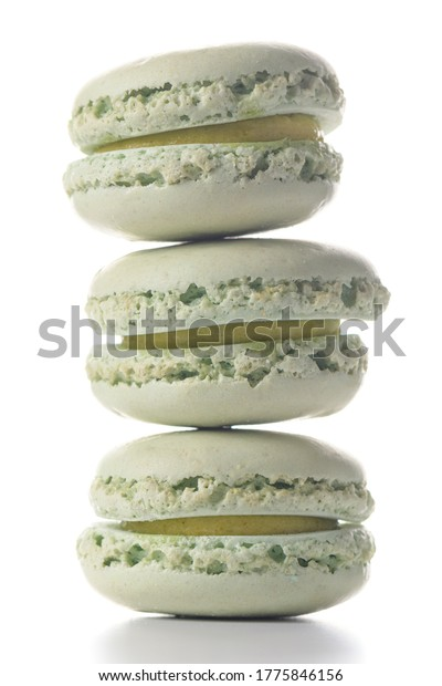 Three mint flavored macaroons standing on top of each other on white background.