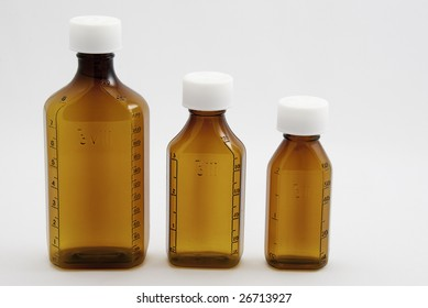 Three mixed size brown medicine bottles on a white background.