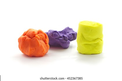 Three Modeling clay balls of different colors isolated on a white background