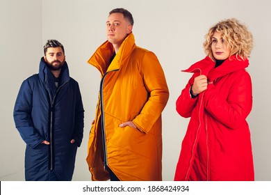 Three models on a white background in warm, winter down jackets. A group photo of two men and one woman wearing colorful clothes on a white background. Stylish winter clothes