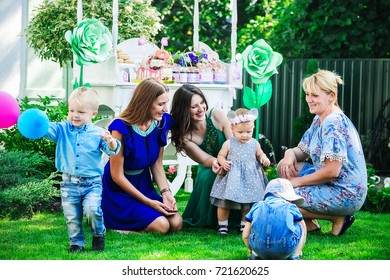 three moms with their children playing on the grass in the yard against the backdrop of a candy bar at a children's party