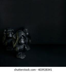 Three monkeys. Monkeys. Signs. See. Speak.  Sculpture. Three monkey isolated on black background. Сlose up. Symbols.