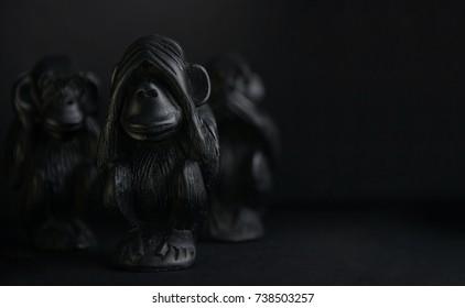 Three monkeys. Monkeys. Signs. See. Speak.  Sculpture. Three monkey isolated on black background. Сlose up. Symbols. ЗЛО.