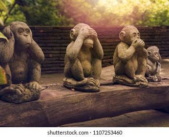 three monkeys statues which have different posts.
