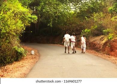 Three monks walking on the road. Gokarna, Karnataka, India.