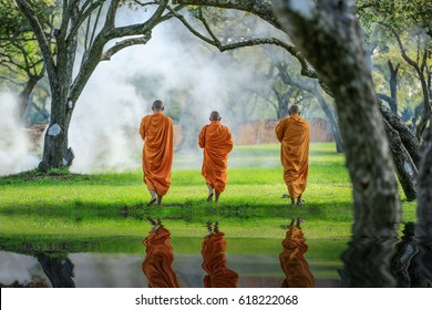 Three monks walking in the park,, thai monk meditating under a tree at Ayutthaya,buddhist temple in Thailand