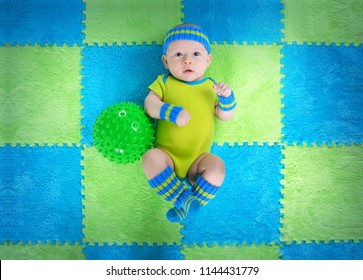 Three month old baby in sports costume lying on a play mat with green ball